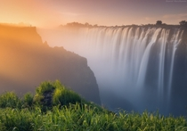 The sun lighting up fog created by the Victoria Falls Zambia  photo by Daniel Korzhonov