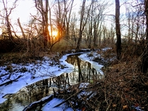 The sun sets over a thawing creek on a chilly winter day - Chester County PA