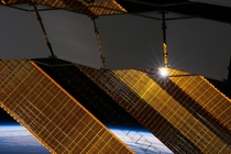 The sun shines through the solar panels of the ISS