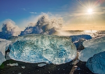 The sun together with the waves smashing against ice blocks at diamond beach in Iceland