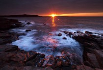The suns rays strike the rocky coast of Acadia National Park Maine