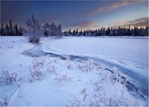 The Umba River frozen and covered with snow Kola Peninsula Russia