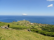 The village of Ponta Delgada on Flores Island Azores with Corvo Island in the distance
