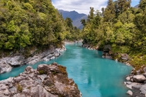 The vivid turquoise water of the Hokitika River rushes through a magnificent granite gorge lined with native bush  New Zealand by Jos Buurmans