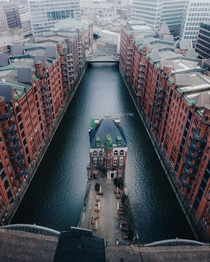 The Wasserschloss in the middle of a canal between the row of historic warehouses in Speicherstadt Hamburg Germany