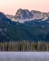 Theres something special about waking up early to watch the mist rise off the lake and see the soft pink sunrise at Stanley Lake Idaho
