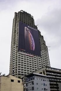 This abandon sky scrapper in Bangkok is now the home for one of the largest billboards Ive seen