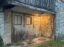 This abandoned stone barn is located in an alley in my hometown Overall its in a bad state of disrepair but the entryway is still illuminated by an old solitary incandescent lightbulb