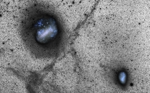This deep view of the Large and Small Magellanic Clouds is actually a combination of two photos captured from ESOs La Silla Observatory The clouds are shown in color as glittering blue holes while the thousands of stars are captured in black and white