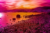 This is an infra red view of a volcanic lake in New Zealand Rotorua You can see a bright orange area in the foreground where a thermal vent is bubbling up through the ground The water here is boiling as it comes out