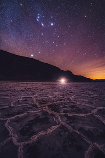 This is Badwater Basin in Death Valley As Orion rises overhead the distant glow from Las Vegas illuminates the salt flats