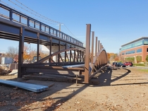 This Under Construction Footbridge will allow people using the Cochituate Rail Trail to walk or bike over Commonwealth Road in Natick MA near the Golden Triangle improving walkability dramatically