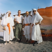 Three Apollo astronauts in survival training clothed with parachute fabric