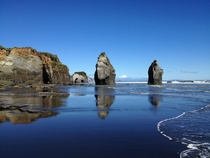 Three Sisters on the black sand of Tongaporutu Beach New Zealand