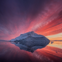 Tranquil waters colored by the reflection of blazing skies in Greenland by Daniel Kordan