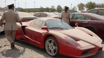 two dubai police officers inspecting an abandoned  million ferrari enzo