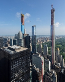 Two helicopters fly near New Yorks pencil-thin skyscrapers