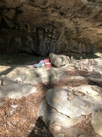 Unsettling abandoned campsite found under a cliff face Someone left behind all their gear their boots and even a message burned into the rocks Album in comments