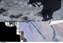 US Astronaut Steve Robinson casts a shadow on Discoverys Thermal Protection Tiles during a spacewalk as part of the STS- mission