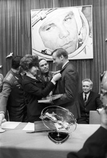 Valentina Tereshkova first woman in space holds Neil Armstrong first man on the moon by the cuff while Yuri Gagarin first man in space looks down on them from the wall in