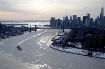 Vessels on the East rivers maneuver through floating ice sheets as the Stature of Liberty stands in a frozen harbor NY
