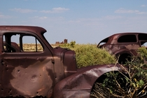 Vintage rusted cars and a crumbling stone building