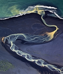 Volcanic river runs to the sea Iceland