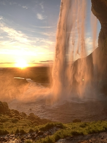 Watching the sunset from behind a waterfall in Iceland