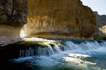 Water flows through the rock formations at Pillar Falls as the sun rises above the Snake River in Twin Falls Idaho