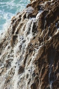 Water runs of a rock after being struck by a wave