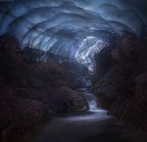 Waterfalls in what appears to be a dimly lit cave in Kamchatka by Daniel Kordan