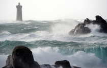 Waves break around the Four lighthouse in Porspoder France Fred Tanneau