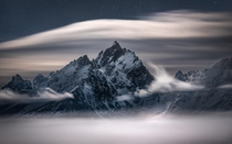 Waves of clouds swirling around the Teton Range on a moonlit night