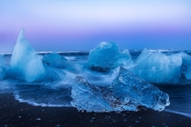 Waves pushing their way past icebergs on the black sand beach of Jkulsrln in Iceland