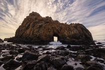 Waves roll through a rock formation at Pfeiffer Beach - Big Sur Coastline California