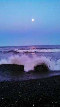 Waxing gibbous over crashing waves at dusk Lake Superior