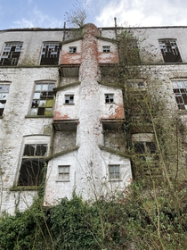 We were exploring an abandoned linen mill in Northern Ireland and saw this structure on the side of the factory does anyone know what its for Each little house type thing is barely big enough to fit a person in each side and there was a floor at each leve