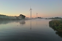 Wind turbines and highway in early morning sunrise and mist - The Netherlands