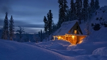 Wintry cabin at sunset