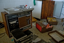 Wonderfully retro woodfaux wood paneled audio equipment at a learning center inside a defunct military gymcommunity center I cant identify what the strange aluminum device on top of the tape recorder is Can anyone else OC x