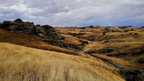 Yellow hills and black rock formations - Poolburn Lake New Zealand
